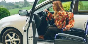 Behinderte Frau steigt aus dem Auto in den Rollstuhl