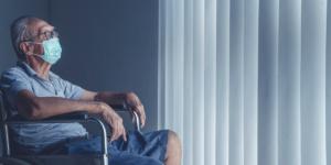 einsamer Mann mit Mundnasenschutz-Maske sitzt im Rollstuhl und schaut zum Fenster raus