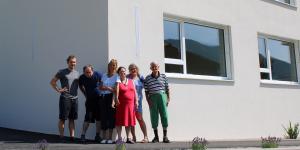 Das Bild zeigt eine Gruppe Menschen vor einem Wohnhaus.