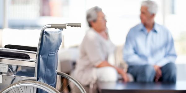 Ein älteres Paar sitzt auf der Couch. Im Vordergrund steht ein Rollstuhl.