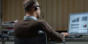 Ein Mann im Rollstuhl arbeitet am Computer